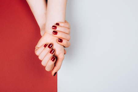 Red beautiful manicure on red ang grey stylish background with copyspace. Flat lay style.