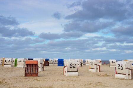 Verlassener Strandkorb am Strand bei bewölktem Himmel Standard-Bild