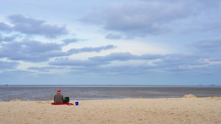 Lonely woman with a red hat is on vacation with a dog on the North Sea beach at low tide in the Wadden Sea