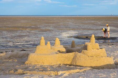 Sandburg am Strand vor Wattenmeer an der Nordsee mit Wolken am blauen Himmel