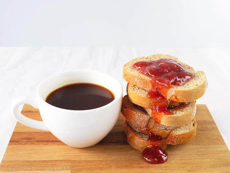 Bread with strawberry jam and coffe on a chopping board. Selective focus. Still life. Copy space.