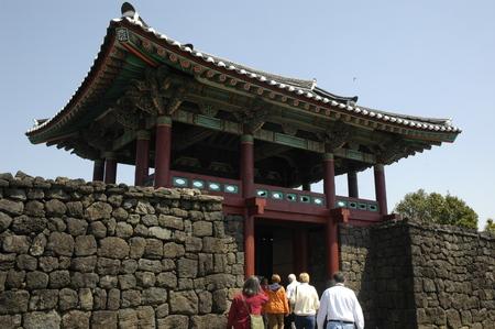 folk village: visitors entering through ornate oriental entrance gate of seongeup folk village. jeju (cheju). sth korea
