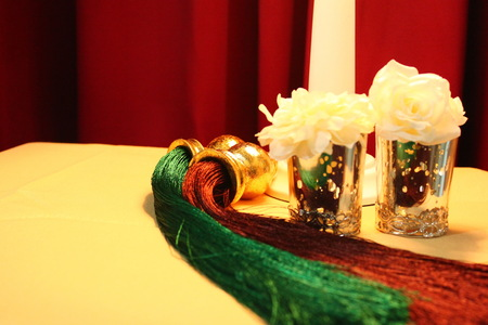 clearer: Table was covered by white blanket and decorated by red and green tassel with white roses. Orange light shone on the table and reflected all of them to clearer.