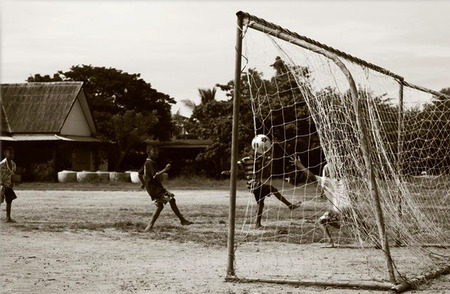 striker: Boys were playing football in the grass field. While striker kicked ball and it was passing goalkeeper into the net. The image was taken right now.