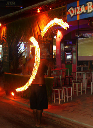 swaying: Fire swinging show which is popular performance of islander in Thailand. It could advert of tourists to stop and look at the show. In the picture, the man was swaying two fire lights in his hands. Editorial