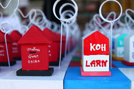 gewgaw: The image is paperweight which is designed to postbox . And another is name of island in Thailand. Beside postcard and magnet, paperweight is  popular souvenir for this island.