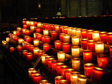 Candles were lighted at Notre Dame church in Paris of France. Candlelight in darkness helped people to clearly see the beauty of architecture in church.