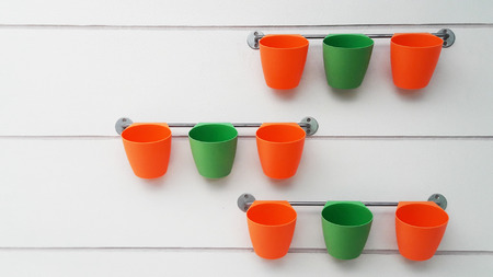 Orange and green flowerpots were hang on railing. But all of them are without flowers for adornment. However, they can make me fresh from their color.