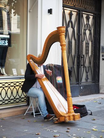During weekend  amateur musicians would display their musical show on street of Paris in France. In this image, the old man was playing his Harp to walker at avenue and hope audiences to give something to him for appreciation.