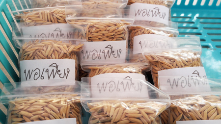 """ample: Plastic bag fully contained paddy and tagged Thai wording """"Por Pieng"""" which means sufficient in English language that was placed in blue basket. Stock Photo"""