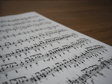musical score: The book which contain notes in staff on full page was placed on wooden desk.