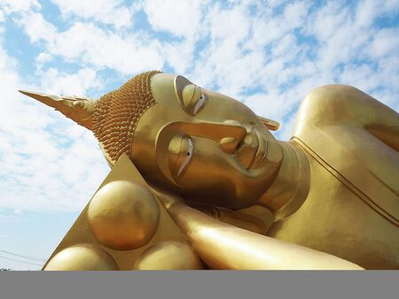 Golden Reclining Buddha statue is placed at Arunyikavas temple that is public property of Thailand. The statue is enshrined outside of chapel and blue sky as background.