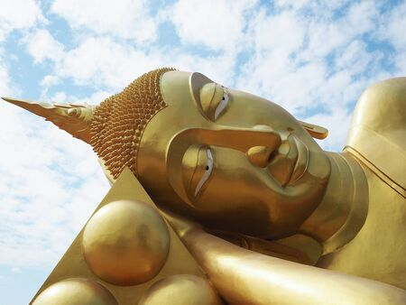 Golden Reclining Buddha statue is placed at Arunyikavas temple that is public property of Thailand. The statue is enshrined outside of chapel and blue sky as background. The image from close up angle. Stock Photo