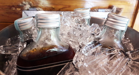 Four tea bottles are frozen in fully ice bucket and placed on wooden table. Stock Photo