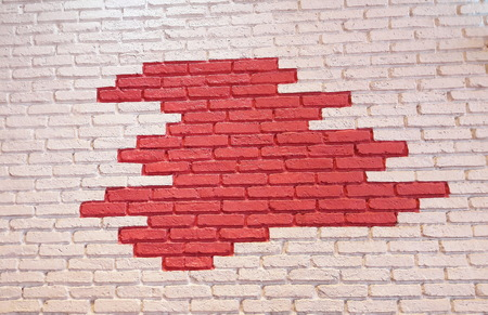Bricked wall was painted by white in contour and red color is in center of it. Stock Photo