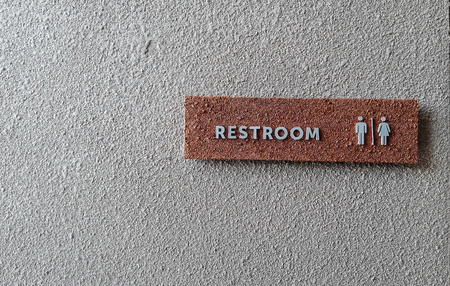 watercloset: Restroom sign is made from red stone which has grey alphabets on in. It is attached with grey wall. This photo was taken from wide angle.