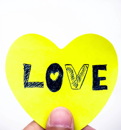 The message of love is written by black ink pen on yellow paper and reader hold it for reading on white background. Stock Photo