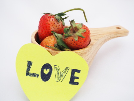 Love word was written on yellow paper and attached on wooden cup which fully contained strawberries on white background. Focusing on one strawberry in cup. Stock Photo