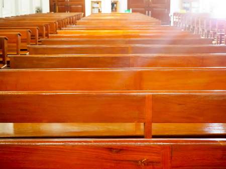 Sun shines the light to pews that are placed in church. Stock Photo