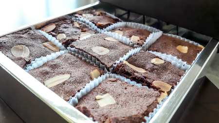 The box contained chocolate brownies. Some of them were eaten and the rest were scattered by thin almond on surface of them. It was placed on wooden table. Stock Photo