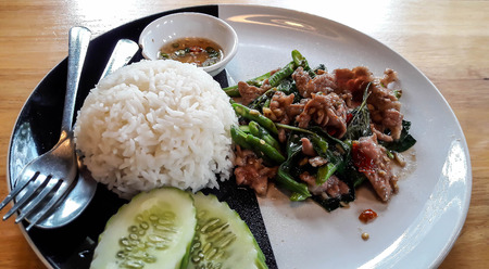 sharply: Rice was served with fried pork and basil on black and white plate. It is favorite menu in Thailand. Chili with fish sauce and cucumber are seasoning.
