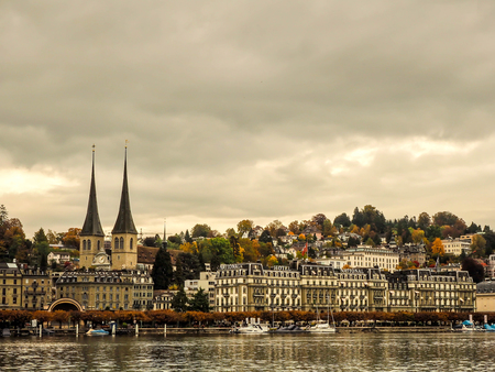 21 Oct 2016, This photo was took from opposite side of Hofkirche where is landmark of Lucerne, Switzerland and it is famous place of tourists for sightseeing. Hofkirche places in between people's houses and hotel while many boats anchored at Reuss river Editorial