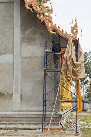 man decorating thai temple