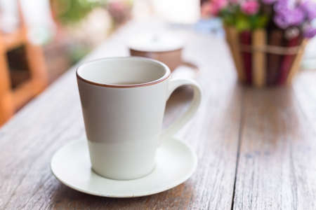 A white cup of coffee on a wooden table