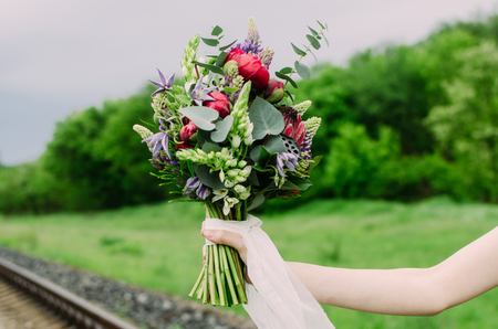 Close up of wedding bouquet with green, red and violet flowers and white ribbon. Bride with wedding bouquet in her hands. Bouquet consists of lupine, peony, protea, eucalyptus and lotus.