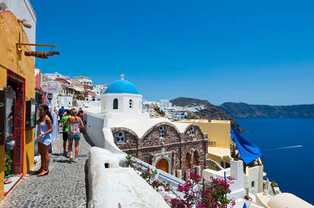 SANTORINI,OIA-JULY 28: Tourists go shopping on July 28,2014 in Oia town on the Santorini island, Greece. Oia is a small town on the islands of Thira (Santorini) and Therasia, in the Cyclades, Greece.