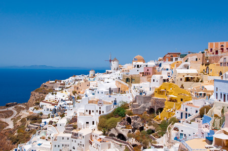 Colorful Oia village on the edge of the caldera cliffs with windmills in the distance on the island of Thira (Santorini), Greece.