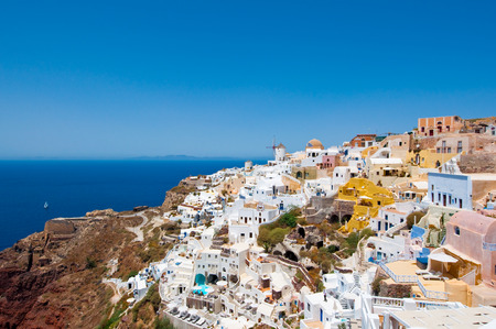 Colorful Oia town on the edge of the caldera with windmills in the distance on the island of Thira (Santorini), Greece. photo