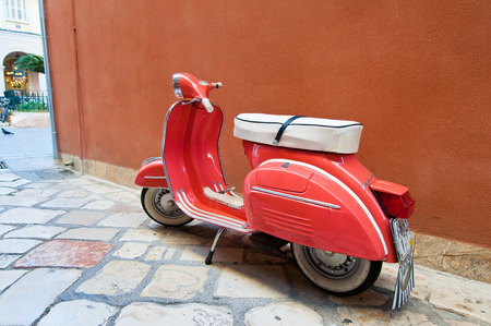 CORFU-AUGUST 22: Vintage Vespa scooter on Kerkyra street on August 22, 2014 on Corfu island in Greece. Vespa is an Italian brand of scooter manufactured by Piaggio.