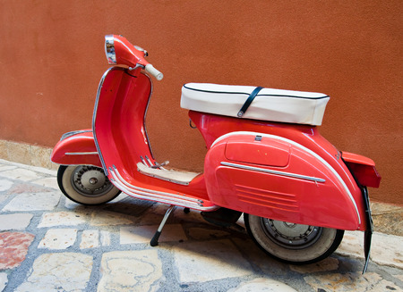 CORFU-AUGUST 22: Vintage Vespa scooter on Kerkyra street on August 22, 2014 on Corfu island. Greece. Vespa is an Italian brand of scooter manufactured by Piaggio.