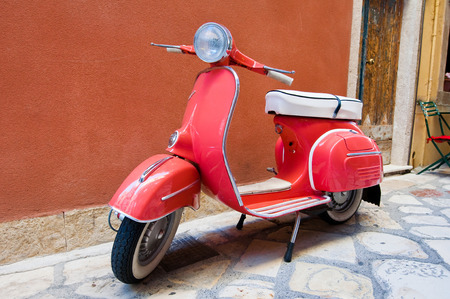 CORFU-AUGUST 22: Vespa scooter parked on Kerkyra street on August 22, 2014 on Corfu island. Greece. Vespa is an Italian brand of scooter manufactured by Piaggio.