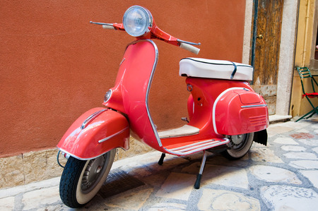 CORFU-AUGUST 22: Classic Vespa scooter parked on Kerkyra street on August 22, 2014 on Corfu island. Greece. Vespa is an Italian brand of scooter manufactured by Piaggio.