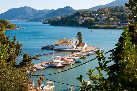 Pontikonisi and Vlacheraina Orthodox monastery from the hilltop of Kanoni on the island of Corfu, Greece. photo