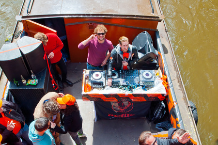 boat party: AMSTERDAM NETHERLANDS APRIL 27: DJ plays music on boat party on Amsterdam canal during King39s Day on April 272 015 in Amsterdam. Kings Day is biggest festival celebrating the birth of Dutch royalty.