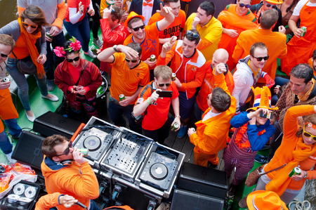 revellers: AMSTERDAM NETHERLANDS APRIL 27: People dressed in orange celebrate King39s Day on a boat on April 272 015 in Amsterdam. King39s Day is the largest openair festivity in Amsterdam. Editorial