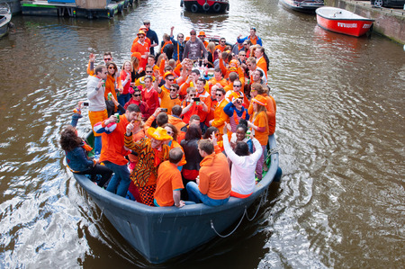 revellers: AMSTERDAM NETHERLANDS APRIL 27: Crowd of people dressed in orange celebrate King39s Day in a boat on April 272 015 in Amsterdam. King39s Day is the largest openair festivity in Amsterdam.