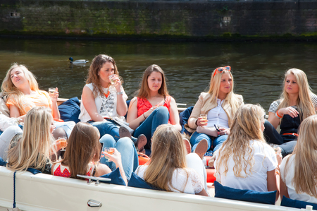 local 27: AMSTERDAM NETHERLANDS APRIL 27: Local girls celebrate King39s Day in a boat on April 272 015 in Amsterdam the Netherlands. King39s Day is the largest openair festivity in Amsterdam.