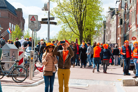 red light district: AMSTERDAM NETHERLANDS APRIL 27: Young couple in orange take picture around red light district on King39s Day on April 2727 in Amsterdam. King39s Day is the largest openair festivity in Amsterdam. Editorial