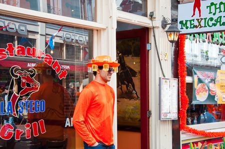 local 27: AMSTERDAM NETHERLANDS APRIL 27: Local in traditional orange on King39s Day on April 2727 in Amsterdam. King39s Day is the largest openair festivity in Amsterdam.