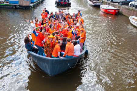 revellers: AMSTERDAM NETHERLANDS APRIL 27: Crowd of local people dressed in orange celebrate King Day in a boat on April 27 2015 in Amsterdam. King Day is the largest openair festivity in Amsterdam. Editorial
