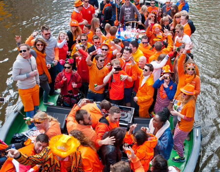 revellers: AMSTERDAM NETHERLANDS APRIL 27: Locals dressed in orange celebrate King Day on a boat on April 27 2015 in Amsterdam. King Day is the largest openair festivity in Amsterdam.