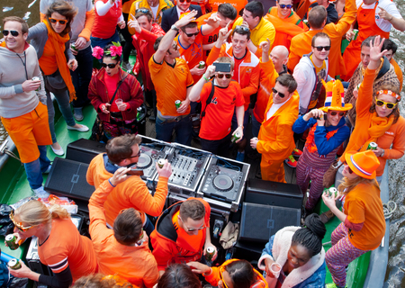 revellers: AMSTERDAM NETHERLANDS APRIL 27: People in orange clothes during King Day on a boat on April 27 2015 in Amsterdam. King Day is the largest openair festivity in Amsterdam.