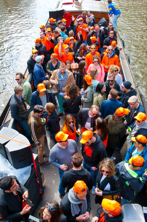 boat party: AMSTERDAM NETHERLANDS APRIL 27: Boat party along Amsterdam canals during King Day on April 27 2015 in Amsterdam. Kings Day is biggest festival celebrating the birth of Dutch royalty.