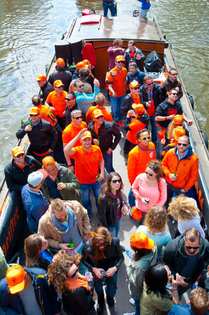 boat party: AMSTERDAM NETHERLANDS APRIL 27: Boat party through Amsterdam canals with unlimited beer during King Day on April 27 2015. King Day is biggest festival celebrating the birth of Dutch royalty.