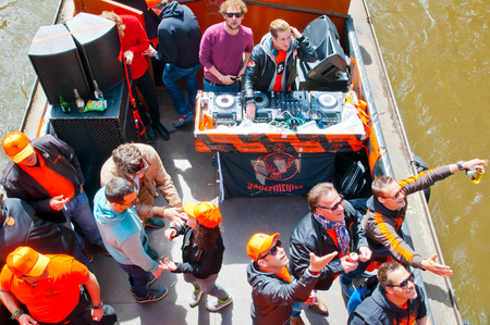 boat party: AMSTERDAM NETHERLANDS APRIL 27: Boat party with DJ on a boat Amsterdam canal during King Day on April 27 2015. King Day is biggest festival celebrating the birth of Dutch royalty.