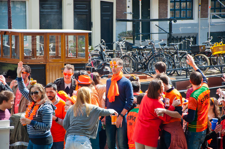 boat party: AMSTERDAM NETHERLANDS APRIL 27: Boat party on Amsterdam canal during King Day on April 27 2015 in Amsterdam. Kings Day is biggest festival celebrating the birth of Dutch royalty.